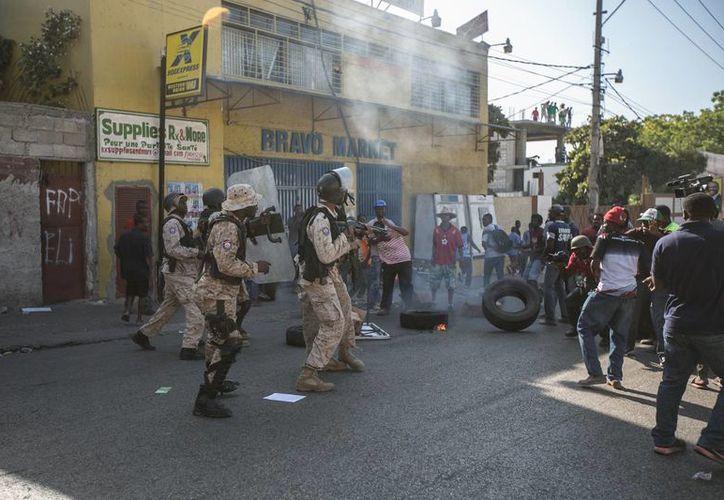 Policías se enfrentan a manifestantes convocados por la oposición haitiana mientras protestan, este martes 19 de enero en Puerto Príncipe. (EFE)