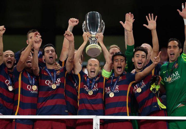 El Barcelona conquistó la Supercopa europea al vencer al Sevilla 5-4, en un partido que se le complicó a los dirigidos por Luis Enrique, en la imagen los catalanes con el trofeo. (AP)