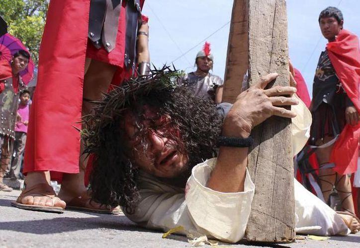 Durante su recorrido, algunos de los devotos flagelados, cuyos rostros estaban ocultos por capuchas, posaron con los turistas para tomarse la foto. (SIPSE)