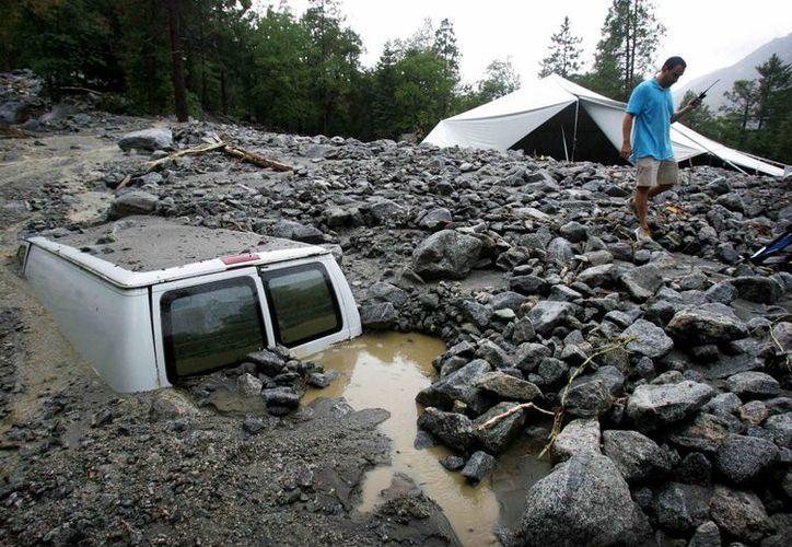 Un hombre inspecciona los daños causados por las tormentas eléctricas en su propiedad. (Agencias)