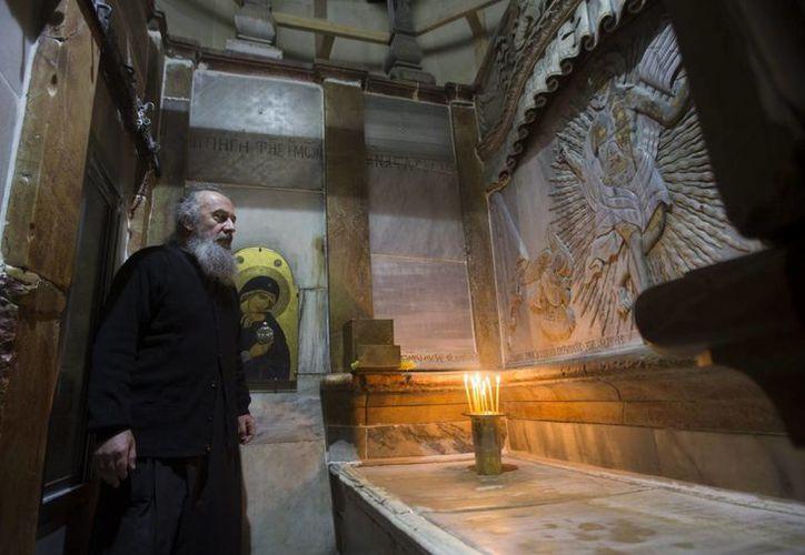 Un clérigo griego ortodoxo junto a la tumba de Jesucristo en la Iglesia de la Santa Sepultura en Jerusalén, Israel. (EFE)