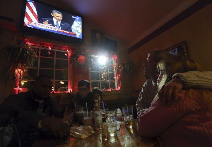 Desde la izquierda:  Julie Lapak y Emslie Scott, de Newtown, observan al presidente Obama emitiendo un discurso de apoyo a las víctimas de la matanza en esa entidad. (Agencias)