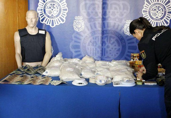 Una policía coloca 45 kilos de heroína y resto de material intervenido, tras la detención de un distribuidor de heroína a gran escala en España. (EFE)