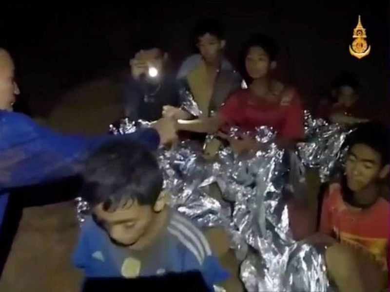 The 12 boys and their coach are seen in the video sitting with Thai navy SEALs in the dark cave.