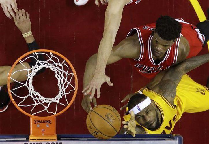 LeBron James (23), de Cavaliers de Cleveland, forcejea contra Jimmy Butler (21), guardia de Chicago Bulls. (Foto: AP)