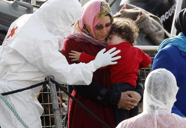 Una mujer sostiene a su hijo al descender de un barco en el fuerte Messina, Sicilia. Socorristas italianos rescataron a 98 migrantes que llevaban 12 días a la deriva. (Foto AP/Antonio Calanni)