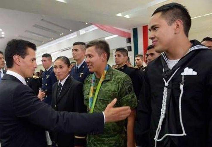 La marchista Lupita González (i), el clavadista Germán Sánchez (c) y el boxeador Misael Rodríguez con el presidente de México previo al  desfile del 16 de septiembre. (Foto de Twitter)