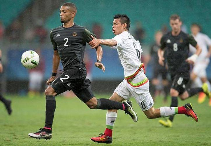Oribe Peralta disputa un balón con el alemán Lars Bender en el partido que México y Alemania empataron a 2 goles,este jueves 4 de agosto. (AP Photo/Arrison Marinho)