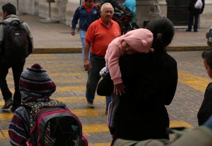 En la Península de Yucatán predominará cielo medio nublado, 40% de probabilidad de tormentas puntuales fuertes en Quintana Roo, intervalos de chubascos en Campeche, y lluvias escasas en Yucatán. Imagen de contexto de un grupo de peatones en el centro de Mérida. (Archivo/SIPSE)