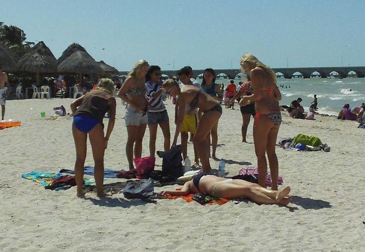 Visitantes extranjeras utilizan la arena como camastro para asolearse. (Manuel Pool/SIPSE)