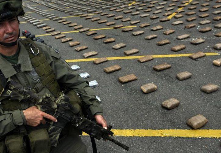 Miembros de la Policía colombiana custodian este lunes 30 de marzo de 2015, 4.1 toneladas de marihuana durante su presentación en una rueda de prensa, en Cali, Colombia. (EFE)