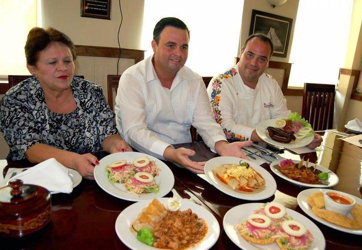 Miriam Peraza, Álvaro Mimenza y David Zetina muestran platillos tradicionales yucatecos. (Milenio Novedades)
