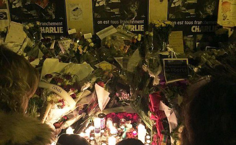 Cientos de ciudadanos han colocado ofrendas florales en instalaciones del semanario satírico francés Charlie Hebdo, en donde ayer se perpetró un mortífero atentado en el que murieron doce dibujantes, periodistas y policías. (Notimex)