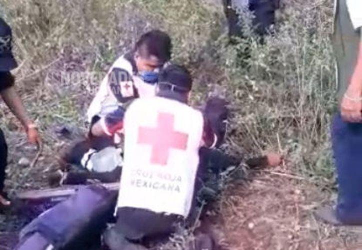 Paramédicos durante las maniobras de resucitación cardio pulmonar a uno de los agentes que salió disparado del vehículo.