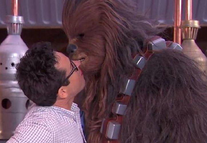 El director de cine J.J, Abrams y Chewbacca se comen un dulce y terminan dándose un beso para cumplir un reto a favor de autistas y a unos meses del estreno de The Force Awakens. (Captura de pantalla de YouTube)