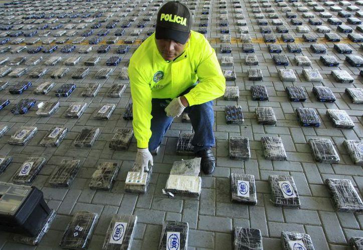 Un policía colombiano inspecciona la cocaína encontrada en un contenedor que tendría como destino final el cártel de Los Zetas, en México. (EFE)