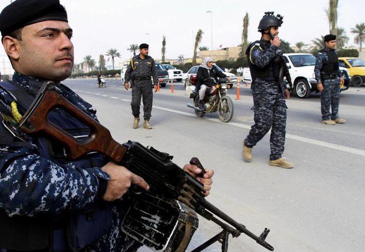 Policías iraquíes montan guardia en un puesto de control en Basora, la segunda ciudad más grande de Irak. (Agencias)