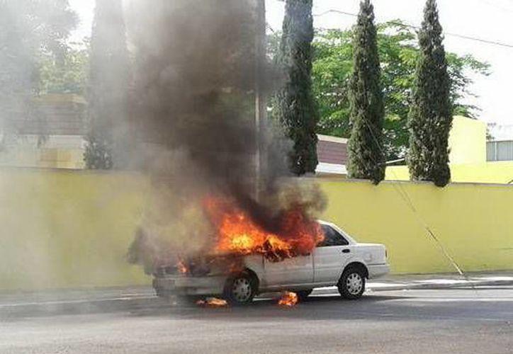 Momento en que el fuego consume el vehículo de la Fiscalía General del Estado en el fraccionamiento Campestre, en el norte de Mérida. (Jorge Sosa/SIPSE)