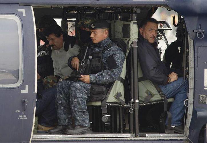 El Chapo Guzmán, líder del cártel de Sinaloa, ya está en el penal de máxima seguridad del Altiplano. En la imagen aparece junto a dos elementos de Marina, cuando apenas era subido al helicóptero que los trasladó a la cárcel. (Agencias)