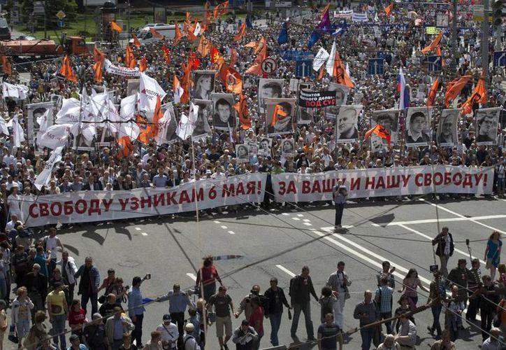 Manifestantes de la oposición rusa sostienen algunos retratos de los presos políticos. (Agencias)