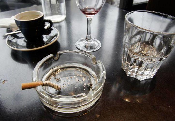 Imagen de un cigarrillo usado en la mesa de un restaurante en París. Un informe dado a conocer hoy,  muestra que el cáncer de pulmón sobrepasó al de seno como el principal causante de muertes de mujeres en países desarrollados. (Agencias)
