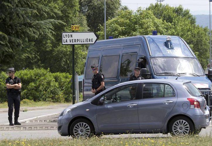Policías custodian el camino a una planta en Saint-Quentin-Fallavier, al sudeste de Lyon, Francia, el 27 de junio del 2015, donde ocurrió un ataque terrorista en que una persona fue decapitada. (AP Foto/Michel Euler)