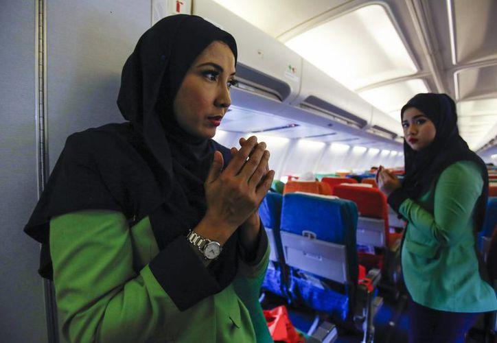 La tripulación de un avión de Rayani Air reza antes de despegar del aeropuerto internacional 2 de Kuala Lumpur en Sepang, Malasia. (Agencias)