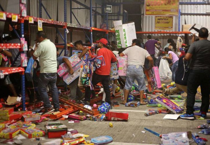 Un grupo de personas saquea un supermercado en el puerto de Veracruz, el miércoles 4 de enero de 2016. Desde que entró en vigor el alza de combustibles en México, se han registrado protestas y manifestaciones que han derivado en actos de violencia y rapiña en establecimientos. (AP/Ilse Huesca)