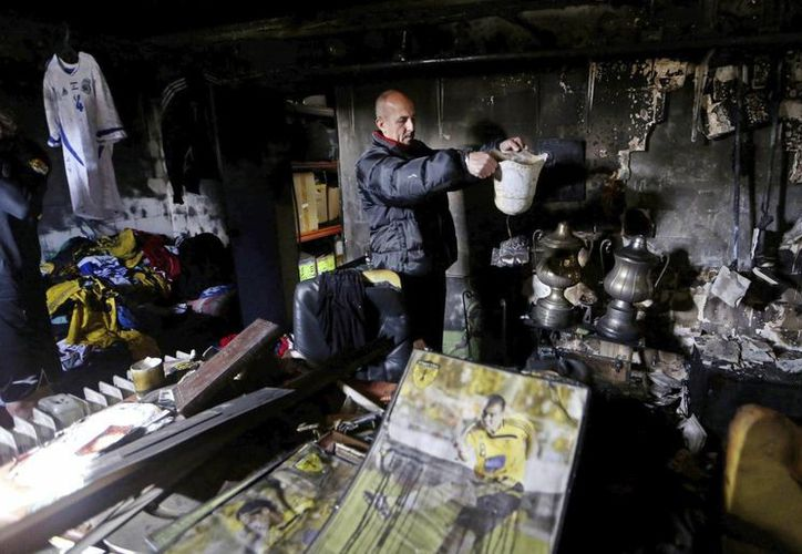 Un miembro del consejo del equipo israelí Beitar Jerusalén inspecciona  la sala histórica que un grupo de pirómanos incendió. (EFE)