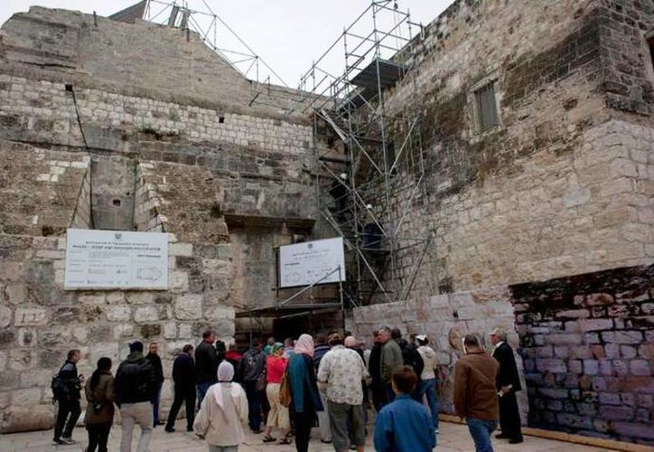 Decenas de turistas, entre andamios, se preparan para entrar en la Basílica de la Natividad, en la ciudad cisjordana de Belén, que se encuentra en reparación. (Agencias)