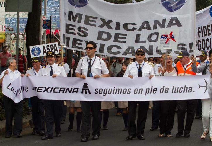 Extrabajadores de la aerolínea llevan a cabo una manifestación frente a Segob. (Notimex)