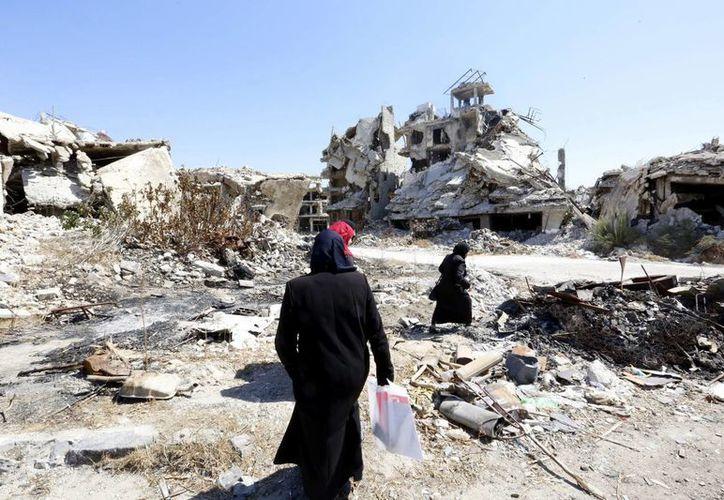 Mujeres sirias caminan entre las ruinas de la ciudad Homs, Siria. (EFE/Archivo)