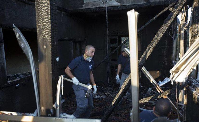 En la imagen, policías israelíes revisan la casa incendiada por presuntos terroristas judíos en Cisjordania. El saldo es de tres personas graves y un menor muerto (AP)
