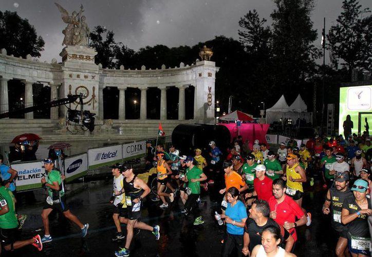 La lluvia matutina que bañó a la Ciudad del país no mermó los ánimos de los participantes en el Maratón. (Notimex)