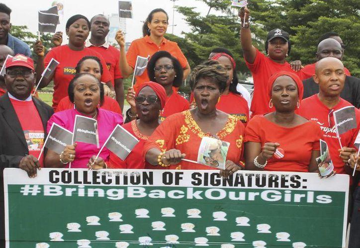 Activistas nigerianos de la Comisión Nacional de Derechos Humanos, Mujeres por la Paz y la Justicia, entre otras organizaciones, durante una protesta en junio, tras el secuestro de 200 niñas en la escuela de Chibok, Nigeria. (EFE)