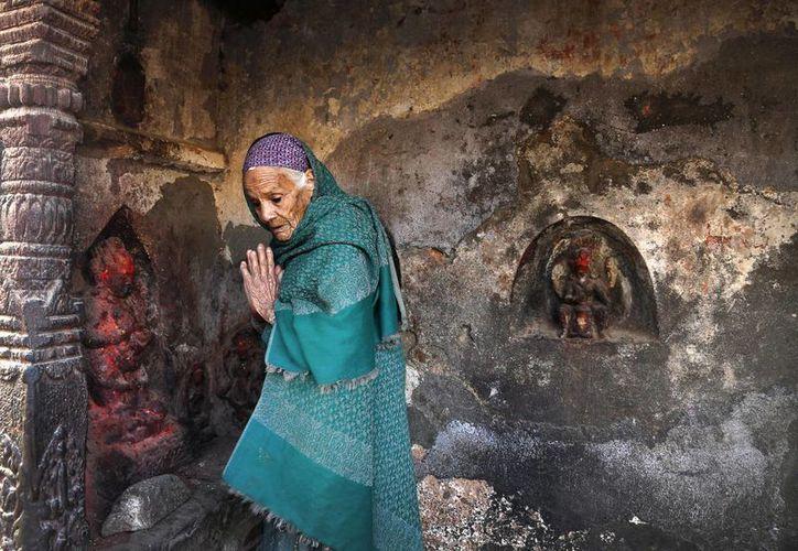 Una anciana nepalí reza en un templo dañado por un terremoto en Katmandú, Nepal. (Agencias)