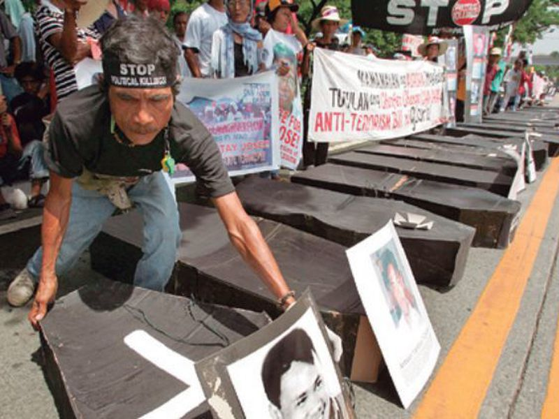A man arranges mock coffins symbolizing the number of their companions killed or abducted, allegedly by the military. (AP)