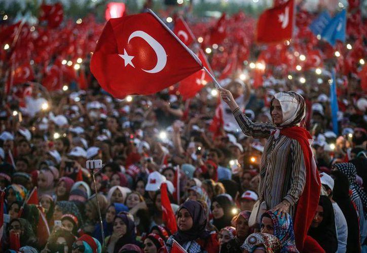 Una mujer turca ondea una bandera de su país durante el discurso del presidente, Recep Tayyip Erdogan, en Estambul. (Foto AP / Emrah Gurel)