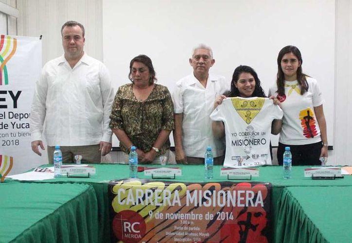Cristina Sosa Rosado, directora de Juventud Misionera Mérida, muestra la camiseta de la competencia durante la conferencia de prensa. (Milenio Novedades)