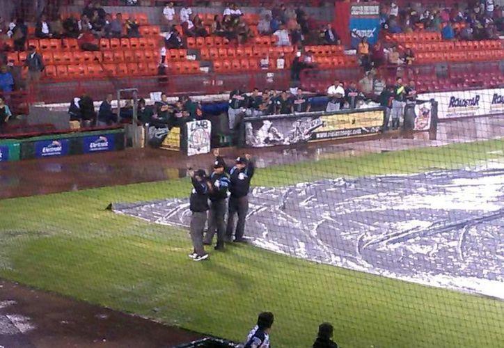 """La lluvia dejó en malas condiciones el diamante del """"Romo Chávez"""", por lo que se suspendió el encuentro al inicio de la primera entrada. En la foto: Los umpires cancelan el primero de la serie entre melenudos y rieleros. (Sipse)"""