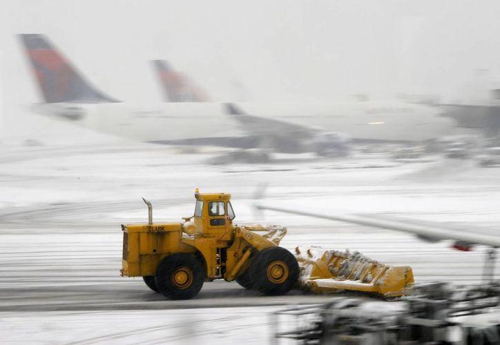 Un quitanieves limpia la pista de aterrizaje y despegue del Aeropuerto Internacional de Newark, NJ. Esta es una de las terminales que interrumpió el tráfico aéreo a causa de la nieve. (AP Photo/Matt York)