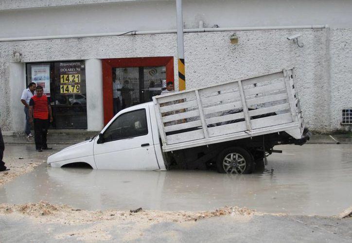 Una camioneta resultó afectada debido a que, por las lluvias, no vio un hueco y cayó en él. (Harold Alcocer/SIPSE)