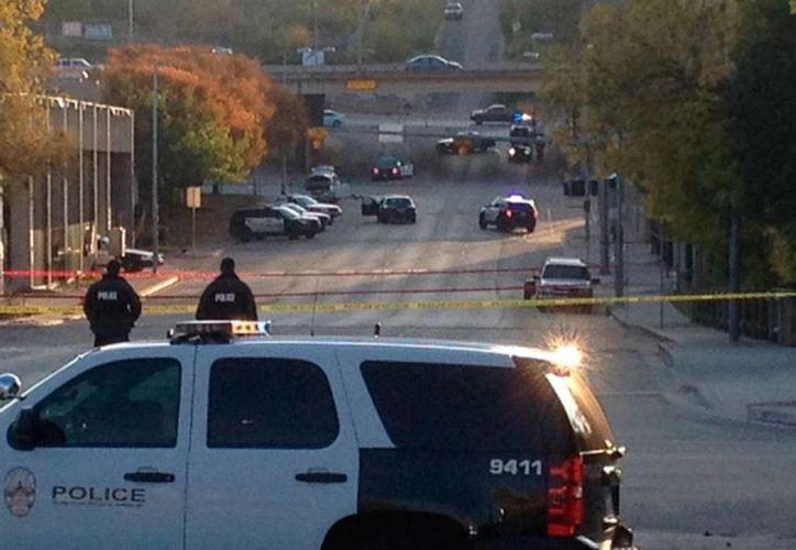 Policía custodia el área donde fue abatido un hombre, quien minutos antes disparó contra varios edificios públicos, entre ellos el Consulado de México. (The Associated Press)