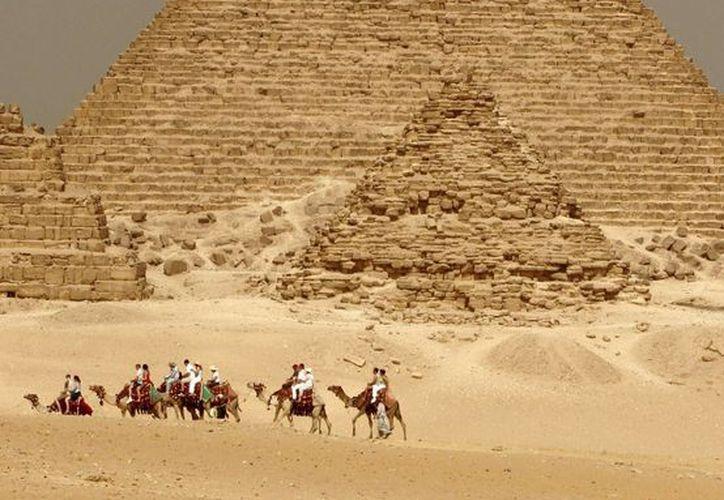 Un grupo de turistas disfruta de una excursión en camello al pie de la pirámide de Micerino. (EFE/Archivo)