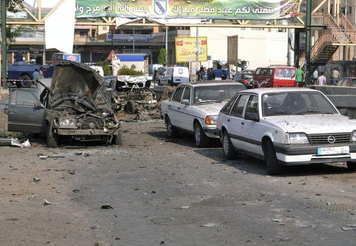 Vista de varios coches destrozados tras una explosión en un puente a la entrada de Trípoli, Líbano en un atentado anterior. (Archivo/EFE)