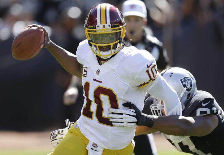 Robert Griffin III, de los Redskins de Washington, trata de eludir a Jack Crawford, tackle defensivo de los Raiders de Oakland. (Agencias)