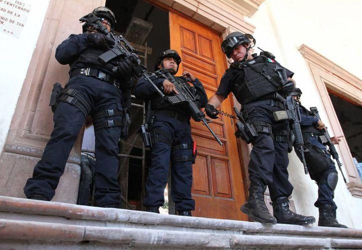 El 6 de enero de 2015, en Apatzingán, Michoacán, ocho civiles murieron por disparos en la calle, algunos cuando intentaban protegerse bajo una camioneta. Imagen de contexto de policías resguardando el Palacio Municipal de Apatzingán.(Archivo/Notimex)