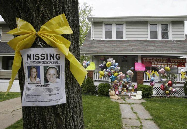 El póster que denunciaba la desaparición de dos de las tres mujeres permanece a las afueras del hogar de una de ellas. (Agencias/Archivo)