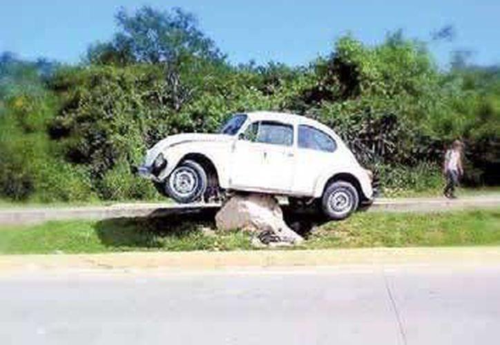 El automóvil Volkswagen Sedán blanco quedó sobre una roca en el camellón central, como si fuera un monumento. (Redacción/SIPSE)