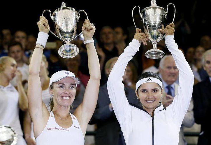 Martina Hingis y su pareja Sania Mirza celebran su triunfo en dobles femenil en Wimbledon. (AP)